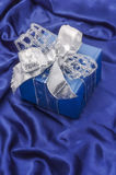 Christmas gift box on blue satin background. Gift box with silver ribbon. Vertical orientation Royalty Free Stock Image