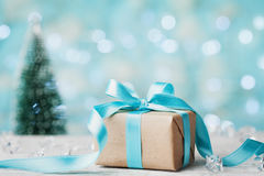 Christmas gift box and blurred fir tree against blue bokeh background. Holiday greeting card. Stock Images