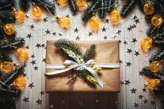 Christmas gift box with a bow and a beautiful glowing garland against the white wooden background with branches stock photo