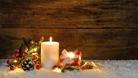 Christmas present with candle, lights and natural decoration Royalty Free Stock Photo