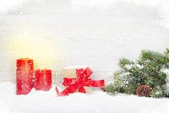 Christmas gift box, candles and fir tree branch. Covered by snow in front of wooden wall. View with copy space Stock Image