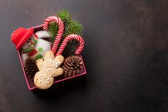 Christmas gift box with candy cane and snowman toy. Christmas gift box with candy cane, snowman toy and snow fir tree on stone table. Top view with space for Stock Photos