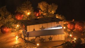 Christmas gift box, Christmas ball on glow bokeh lights background. From the gift comes a magical shine stock footage