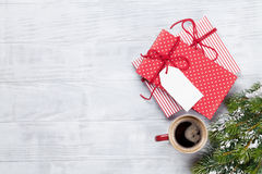 Christmas gift box, coffee cup and fir tree. On wooden background. Top view with copy space Royalty Free Stock Photos