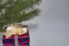 Christmas gift box with a cream bow on a gray background and gre Royalty Free Stock Photo