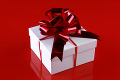 Christmas gift box with a dark-red ribbon bow Stock Photos