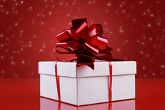 Christmas gift box with a dark-red ribbon bow Royalty Free Stock Photography