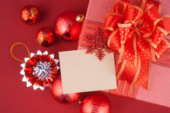 Christmas gift box with decorations and card on red background Stock Photography