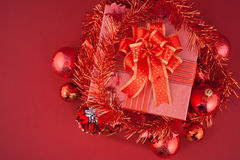 Christmas gift box with decorations and color ball on red background Stock Photography