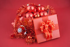 Christmas gift box with decorations and color ball on red background Royalty Free Stock Image