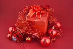 Christmas gift box with decorations and color ball on red background Stock Photos