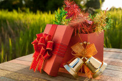Christmas gift box with decorations on wood table in sunset Stock Photography