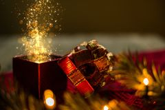 Christmas gift box with gold particle lights magic on red scraf and Christmas tree on wood desk.  stock image