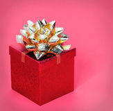 Christmas Gift Box with Gold Ribbon Bow, over red Stock Photography