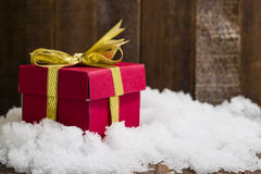 Christmas gift box with a gold ribbon bow on snow Stock Photo