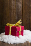 Christmas gift box with a gold ribbon bow on snow Royalty Free Stock Photography