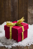 Christmas gift box with a gold ribbon bow on snow Stock Photography