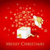 Christmas gift box with gold ribbon and flying sno Stock Photography