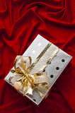 Christmas gift box with gold ribbon. Christmas gift box on satin red background. Gift box with gold ribbon. Horizontal orientation Stock Photo