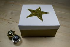 CHRISTMAS GIFT - GIFT BOX WITH GOLDEN STAR. Gift box with golden star and two jingle bells Stock Photos