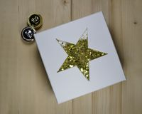 CHRISTMAS GIFT - GIFT BOX WITH GOLDEN STAR. Gift box with golden star and two jingle bells Stock Photography