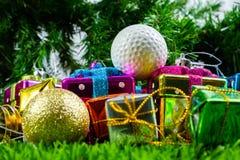 Christmas gift box and golf ball on grass