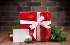 Christmas gift box and greeting card. Christmas gift box, greeting card and fir tree branch on wooden table royalty free stock photo