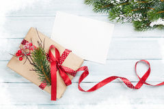 Christmas gift box and greeting card. On wooden background. Top view with copy space Stock Photos