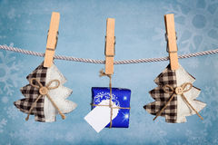 Christmas gift box hanging on clothesline. With fabric tree Stock Image