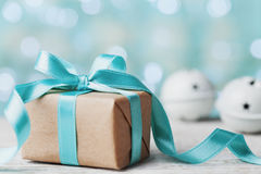Christmas gift box and jingle bell against blue bokeh background. Holiday greeting card. Stock Photography