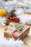 Christmas gift box with New Year's and Christmas decoration midst fruits and tinsel. Royalty Free Stock Photos
