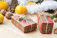Christmas gift box with New Year's and Christmas decoration midst fruits and tinsel. Royalty Free Stock Images