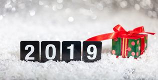 Christmas gift box and new year 2019, on snow, abstract bokeh lights background. Copy space stock images