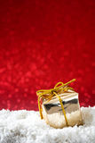 Christmas gift box ornaments on snow and red glitter background Stock Photo