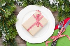 Christmas gift box over dinner plate, silverware, fir tree Stock Images