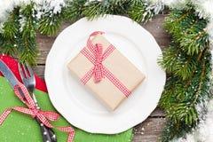 Christmas gift box over dinner plate, silverware, fir tree Stock Photography