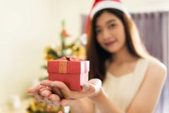 Christmas gift box for party. Closeup Xmas gift box on beautiful Asian woman hands with Santa Claus hat near a Christmas tree with white copy space for text royalty free stock images