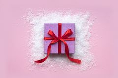 Christmas gift box. Pink gift boxin snow. pink background. Flat lay with copy space royalty free stock images