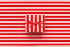 Christmas gift box on pink and red striped wrapping paper. Christmas gift box on red and pink striped wrapping paper. Minimal design background for New Year royalty free stock photos