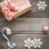 Christmas gift box with pink ribbon and ball, decor from snowflakes, silver ribbon and decor around. Stock Images