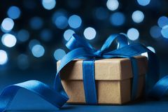 Christmas gift box or present against blue bokeh background. Holiday greeting card. Stock Images