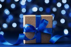 Christmas gift box or present with bow ribbon against blue bokeh background. Magic holiday greeting card. Royalty Free Stock Images