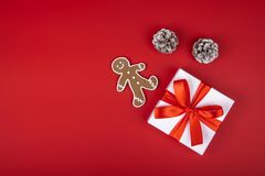 Christmas gift box present on red background with ribbon bows and festive holiday decorations. Horizontal bottom border. Copy space stock photography