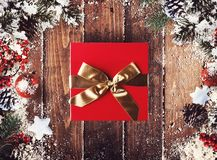 Christmas gift box presented in the middle of Christmas decorations on wooden planks. Xmas decoration grunge background with balls for xmas tree and star royalty free stock images