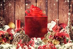 Christmas gift box presented in the middle of Christmas decorations on wooden planks. Xmas decoration grunge background with balls for xmas tree and star royalty free stock photos