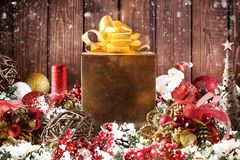 Christmas gift box presented in the middle of Christmas decorations on wooden planks. Xmas decoration grunge background with balls for xmas tree and star stock photo