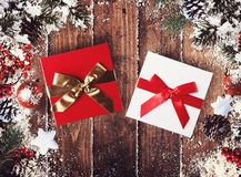 Christmas gift box presented in the middle of Christmas decorations on wooden planks. Xmas decoration grunge background with balls for xmas tree and star royalty free stock photo