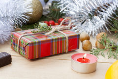Christmas gift box and red candle with New Year's and Christmas decoration midst fruits and tinsel Stock Photos