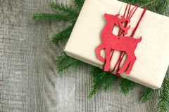 Christmas gift box with red reindeer as toy and spruce tree on wooden board. Top view. Royalty Free Stock Images