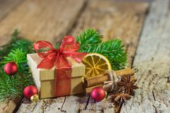 Christmas gift box with red ribbon bow and decorations on wood royalty free stock photos